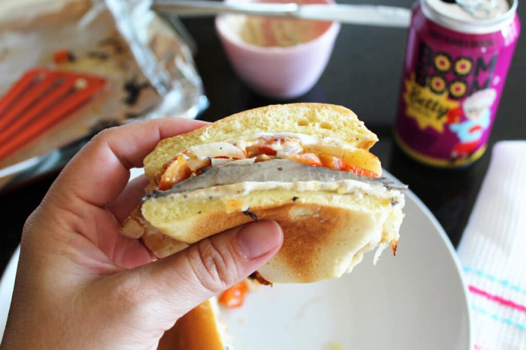 a hand holding a portobello mushroom burger that has been cut in half. staged area behind it.
