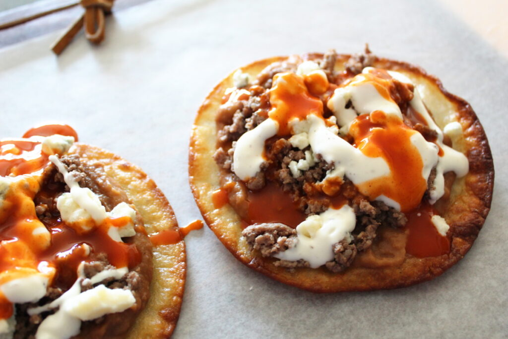 side shot of fried flour tortillas with ground beef, beans, blue cheese, and buffalo sauce