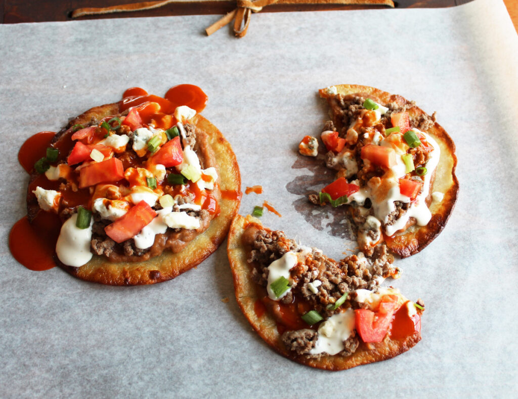 side shot of four b's tostadas one cut in half ready to eat