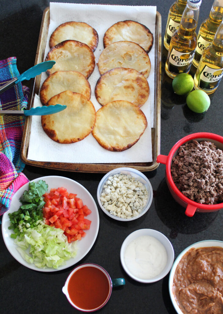 overhead shot of tostadas and ingredients like ground beef, beans, and toppings