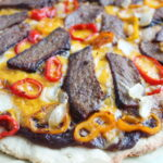 Closeup of steak and sweet peppers on a homemade pizza crust