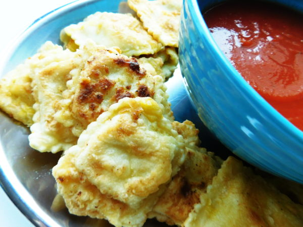 St. Louis Ravioli or Fried Ravioli on a plate with spaghetti sauce ready to serve!