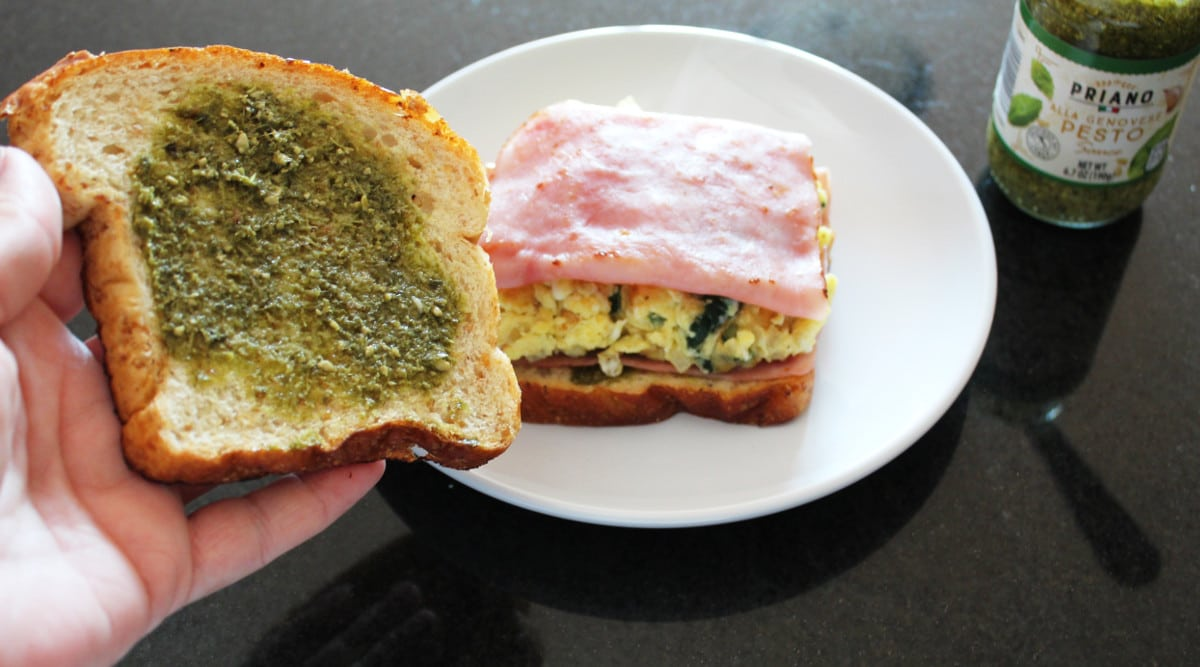 a piece of bread spread with pesto and a ham and spinach breakfast sandwich and jar of pesto off to the side