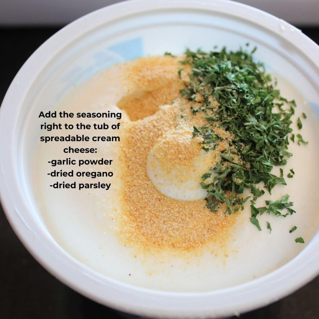 overhead shot of a tub of spreadable cream cheese with herbs in it. descriptive text of ingredients overlay.