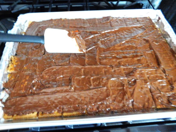 Chocolate being spread over saltine crackers.