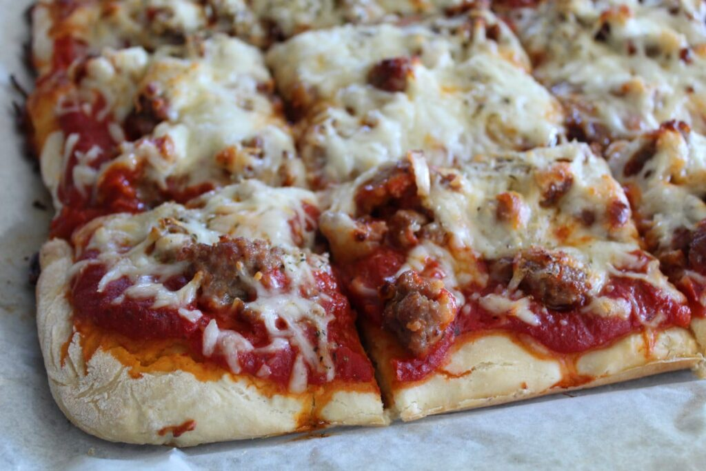 zoomed in side shot of thick crust sausage pizza cut into squares on a piece of parchment paper.
