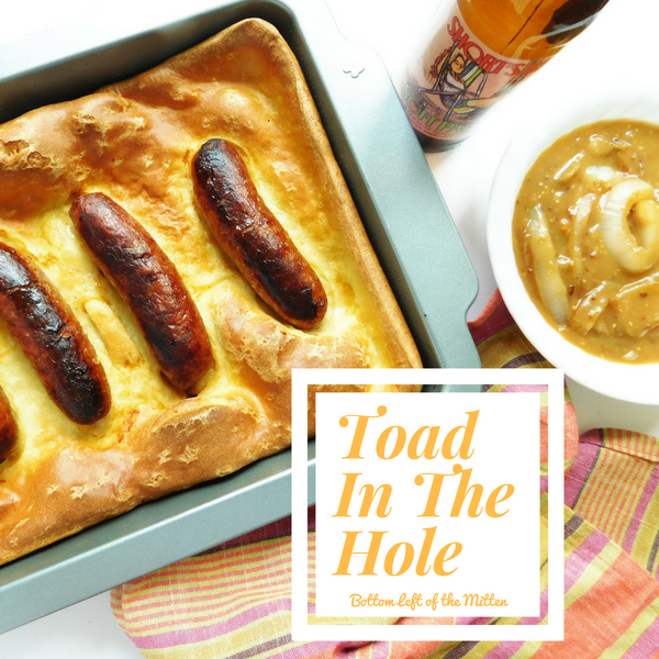 Toad In a Hole in a pan with a craft beer and dish of mustard-onion gravy off to the side.