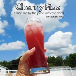 Cherry Fizz in a tall glass with ice and a straw