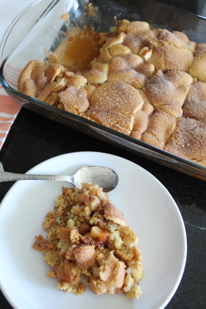 styled long shot of sugar cookie apple cobbler in a pan and on a plate.