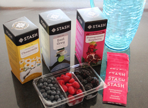 Stash Tea boxes, a pitcher, berries and tea bags laid out on a counter.