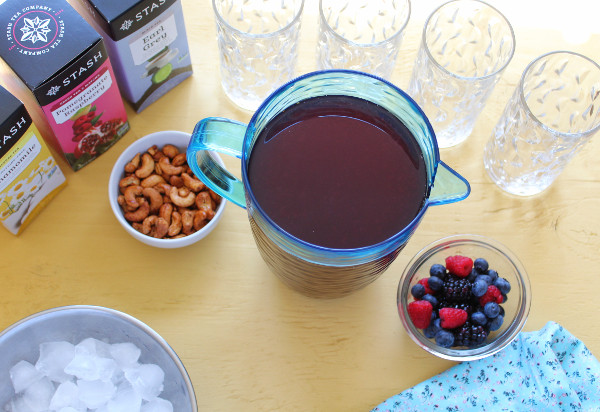 Berrylicious Sweet Tea in a pitcher with Stash Tea in the background, snacks, ice and more berries for serving