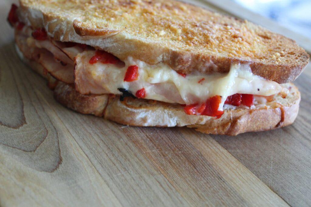 zoomed in side shot of a roasted red pepper turkey sandwich on a cutting board.