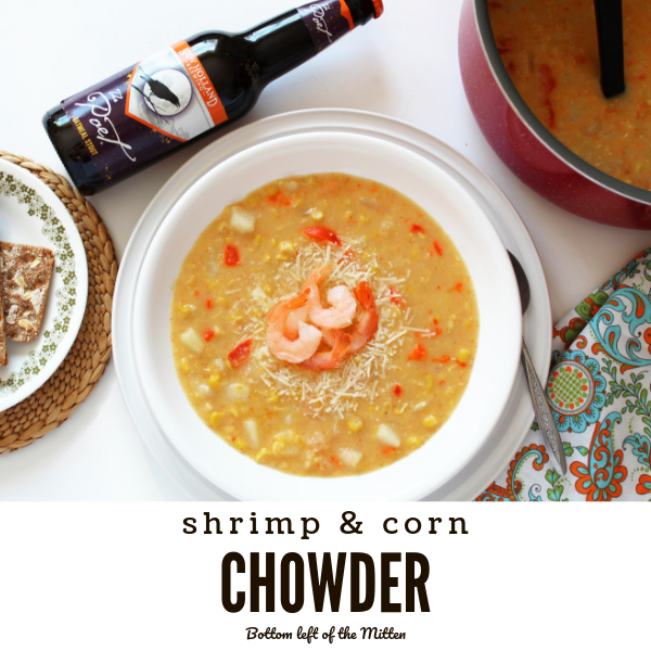 Shrimp and Corn Chowder in a bowl with a craft beer and buttered crackers off to the side.