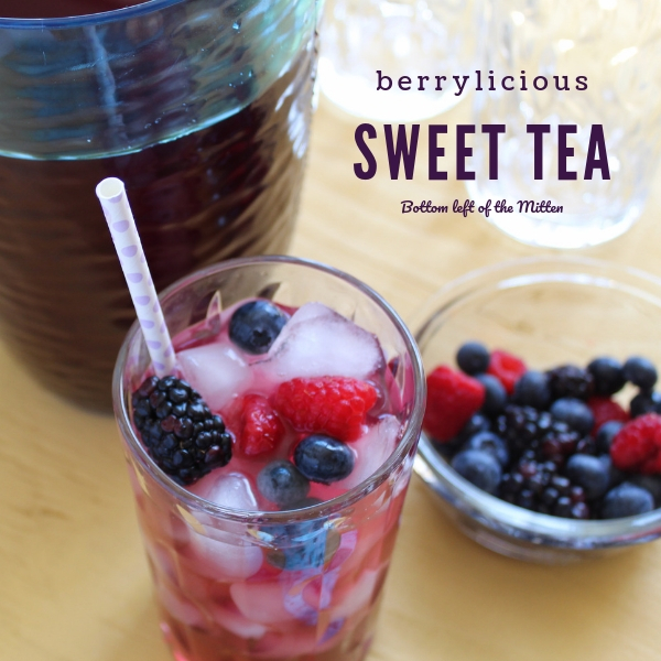 A big glass of Berrylicious Sweet Tea with a pitcher of sweet tea behind it and a cup of berries off to the side.