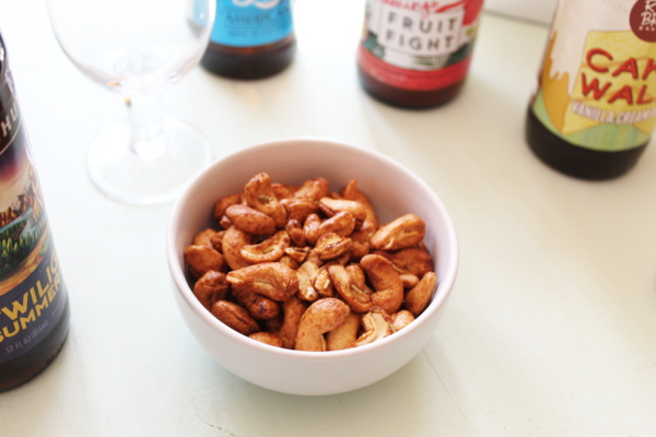 Some cashews for snacks with a selection of craft beer behind them.