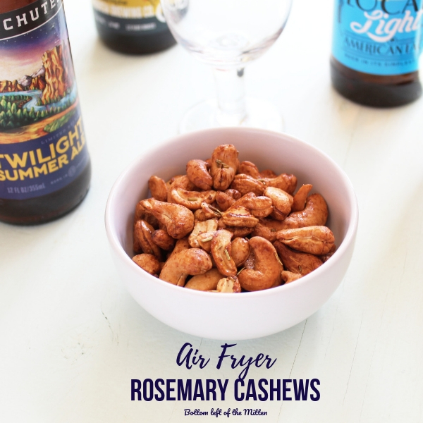 Air Fryer Rosemary Cashews ready to snack on with craft beer in the background.