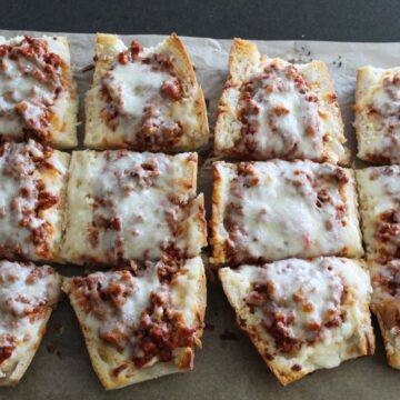 overhead shot of lasagna French bread pizza on a baking sheet.