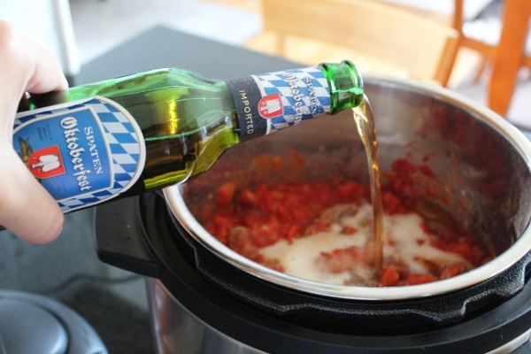 Oktoberfest beer being poured into an instant pot for a beanless beef beer chili