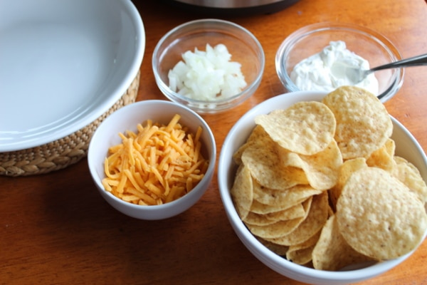 Tortilla chips, cheese, onions and sour cream for toppings on chili.