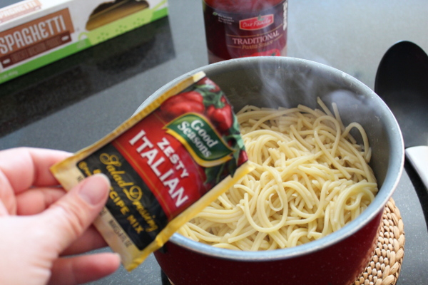 Spaghetti noodles being mixed with Zesty Italian Dressing Mix