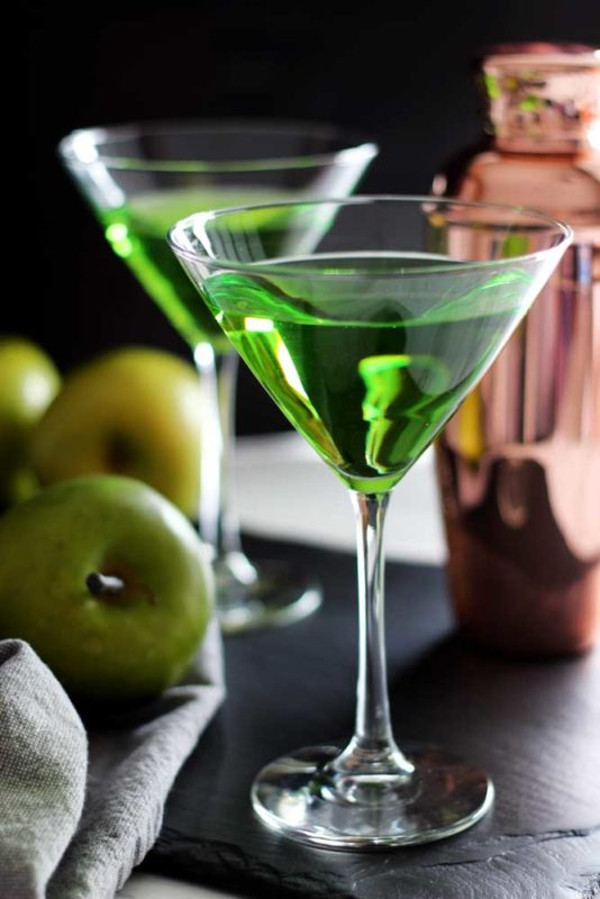 side shot of an apple martini wtih a shaker and green apples off to the side