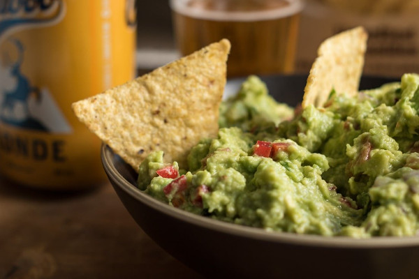 side shot of guacamole with tortilla chips