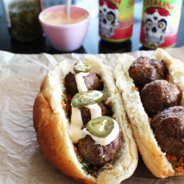 cajun meatball subs pictured with bowls of toppings and two Cervezas in the background