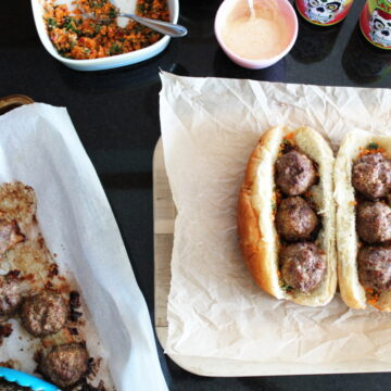 overhead shot of Cajun Meatball Subs on a platter with a baking sheet with cooked meatballs on it and mayo and relish off to the side