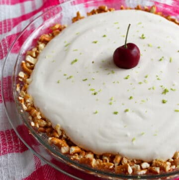 cherry limeade pretzel pie in a pie pan with lime and a cherry on top