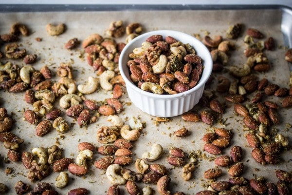 shot of herbed nuts in a bowl and spread around the bowl
