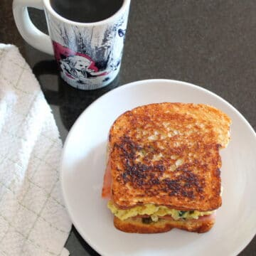 Ham & Spinach Breakfast Sandwich on a white plate with a cup of coffee a towel and jar of pesto around it, shot from overhead