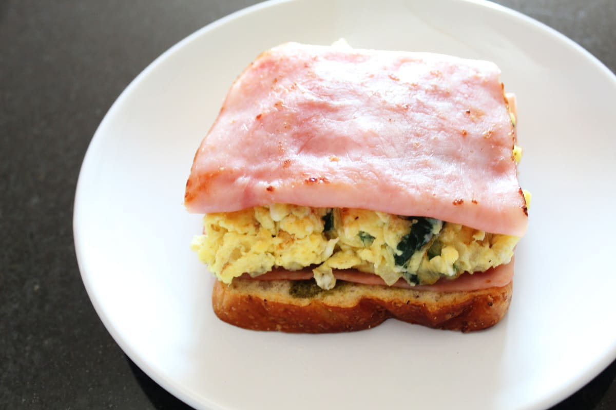 bread ham eggs and spinach on top of a white plate, shot from the side