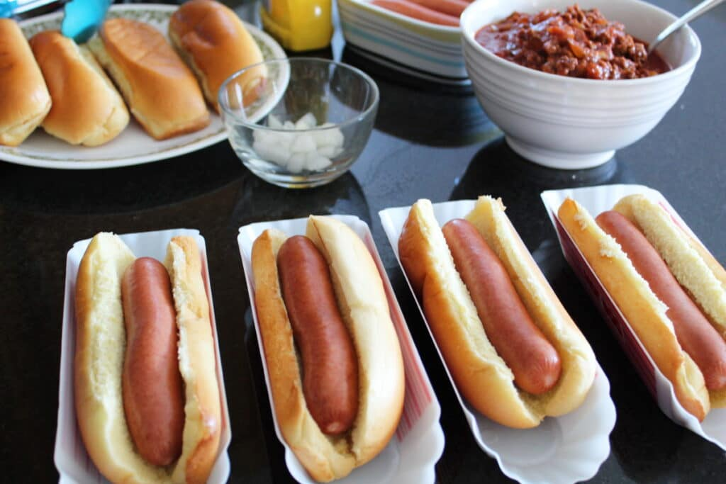 all-beef hot dogs in buns in hot dog containers with chili chopped onions and hot dog buns in the background, shot from the side