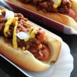 closeup of Michigan hot Dogs in containers topped with Michigan Hot Dog Sauce mustard and onions, shot from the side.