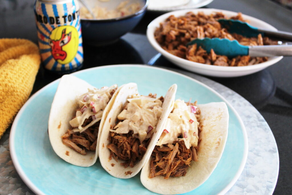 pulled pork tacos with apple coleslaw on a plate with a plate of pork and a beer in the background.