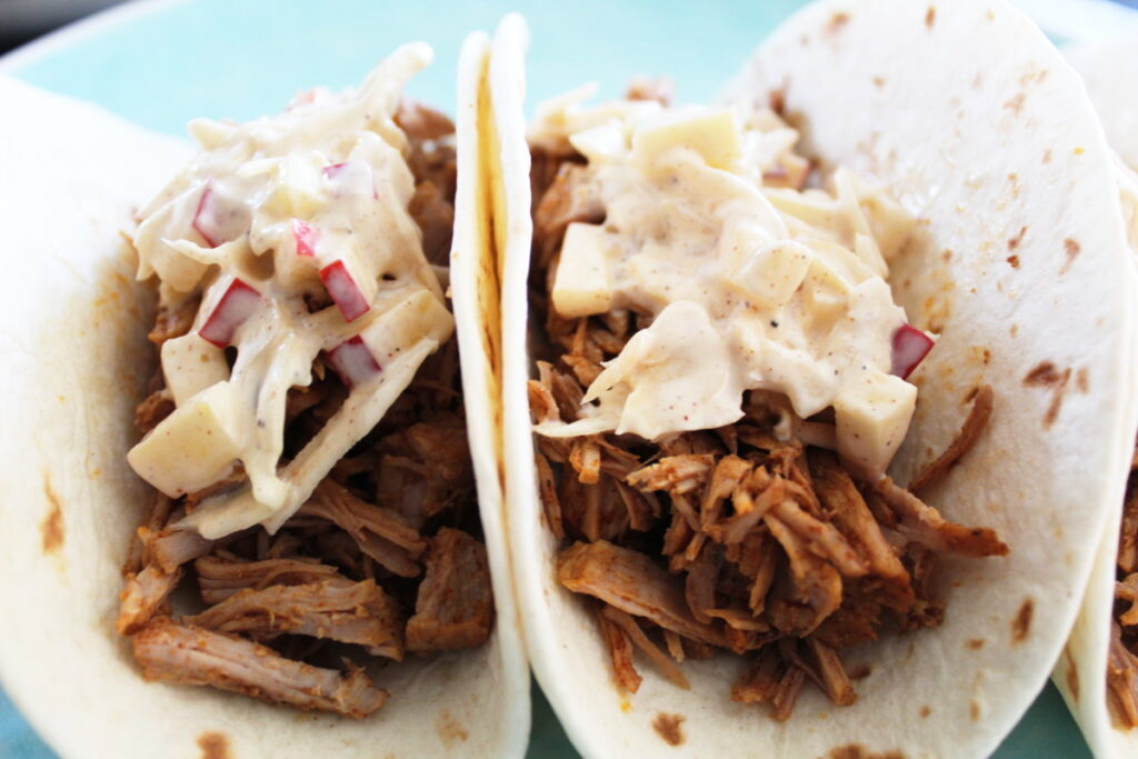 side zoomed in shot of beer-braised pork tacos with apple coleslaw on top in soft tortillas.