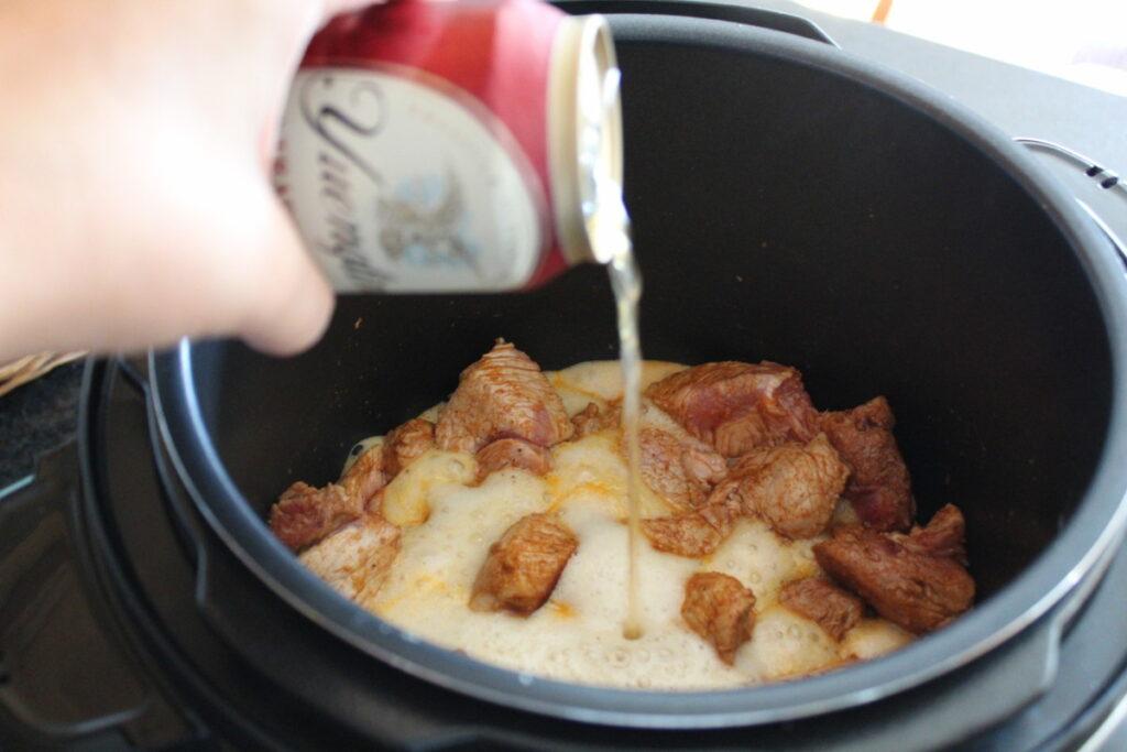 beer being poured over cubed pork in a pressure cooker pot