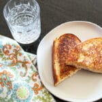 overhead shot of a toasted tuna & cheese sandwich on a plate with a napkin and glass of seltzer next to it