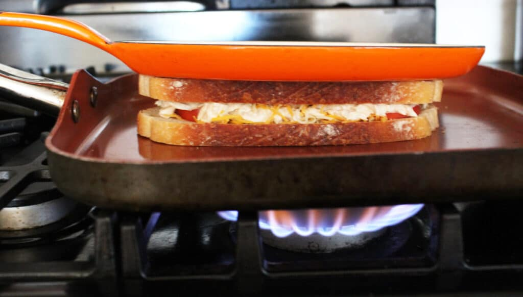 a toasted tuna and cheese sandwich on a griddle pan with a heavier pan on top on top of a lit stove