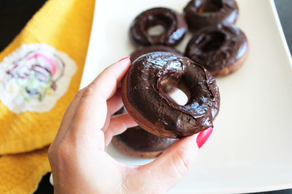 zoomed in shot of a hand holding a death by dark chocolate donut with a platter of more donuts and a towel next to it in the background