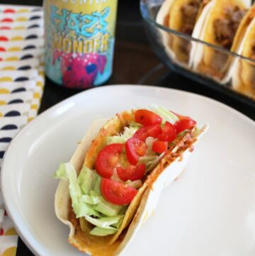 a plate with a taco on it with a pan of double deluxe tacos a beer and a cloth napkin next to it