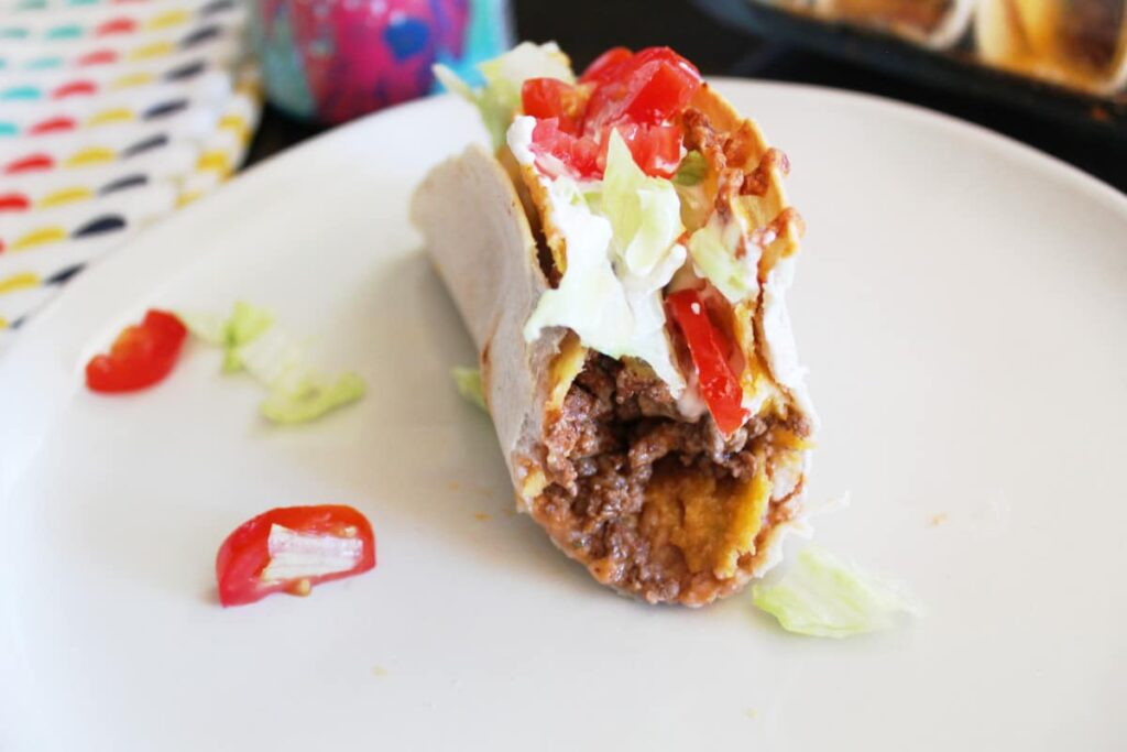 a double deluxe taco that has a bite out of it on a plate with a beer and cloth napkin next to it