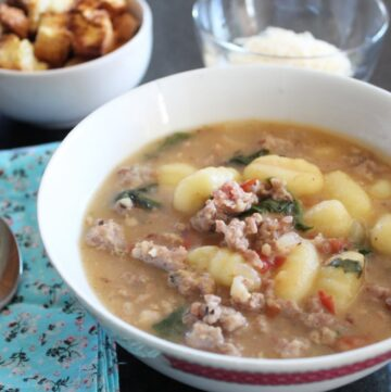 a bowl of gnocchi sausage and spinach soup wiht a cloth napkin and spoon next to it and bowls of croutons and parmesan cheese in the background