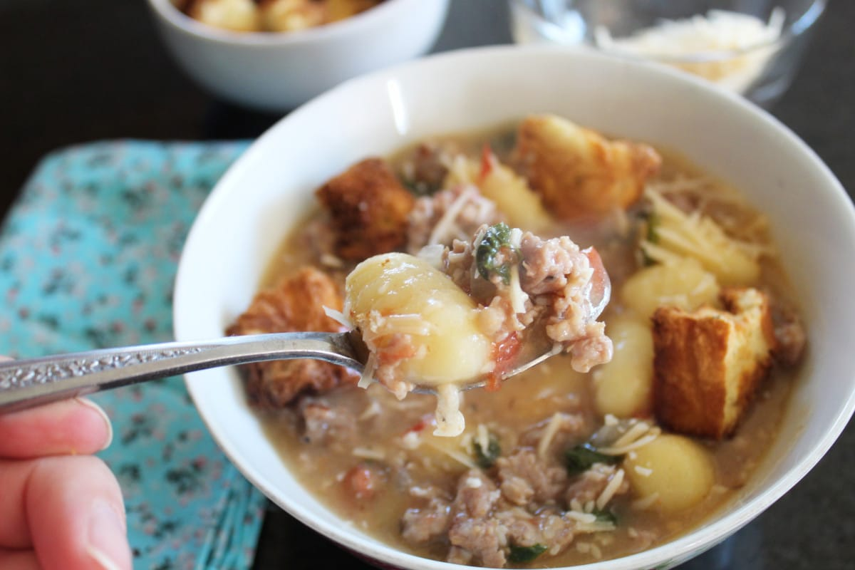 Gnocchi, Sausage & Spinach Soup in a bowl and a close up of it on a spoon.