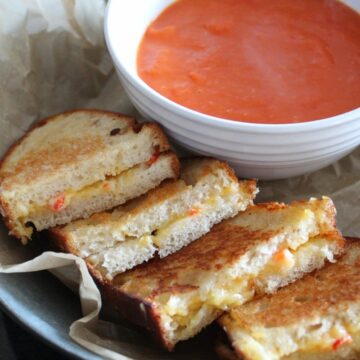tomato and roasted red pepper soup in a bowl with sliced pimento grilled cheese sandwiches next to it on a tin tray with parchment paper