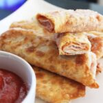 a side shot of pizza spring rolls on a plate with a cup of pizza sauce next to it and a copy of a cookbook i the background