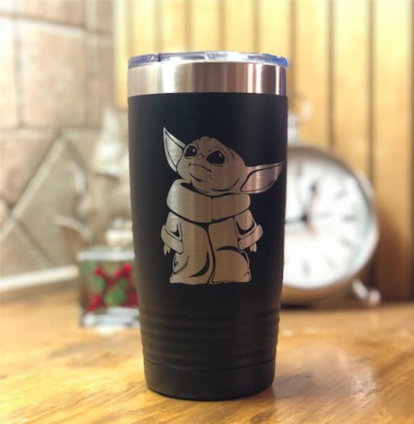 side shot of a Baby Yoda Tumbler on a table with a clock in the background