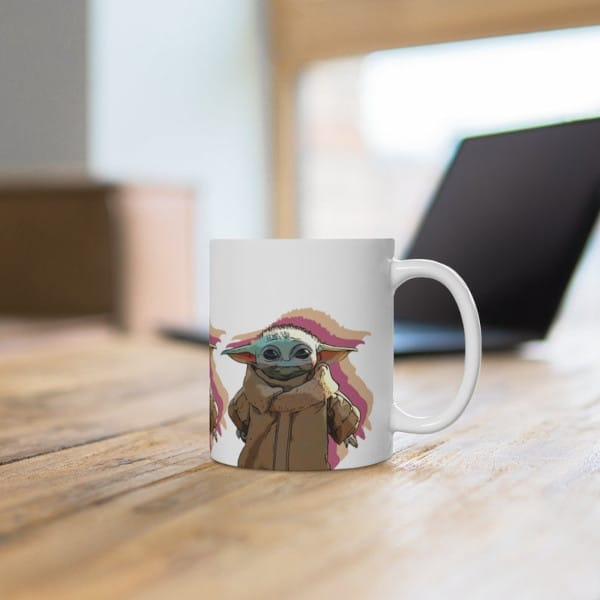 side shot of a Baby Yoda Mug on a table with a computer in the background
