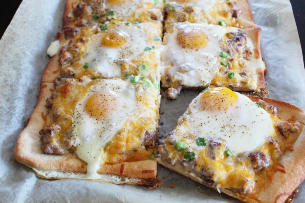 side shot of a breakfast pizza that has been cut into slices on a baking sheet with parchment paper