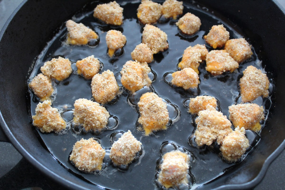 cheese cruds being fried in a cast iron pan with oil